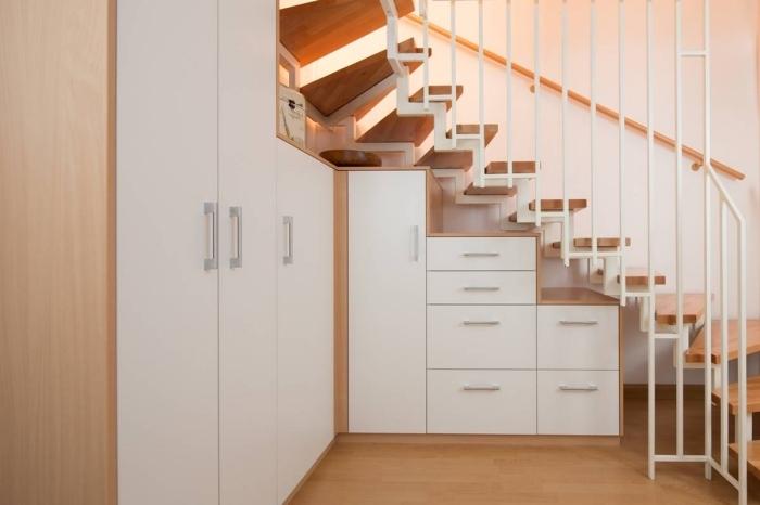 aménagement sous escalier avec garde-robe et armoires d'angle en bois et portes blanches
