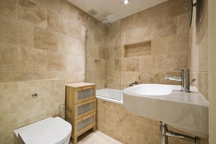 salle de bain en pierre, vasque suspendue blanche, plafond blanc, placard en bois