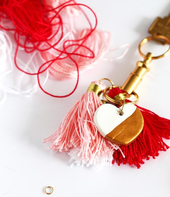 exemple de diy porte clé couleur dorée avec pompons à franges rose et rouge et petit coeur en pate fimo blanc et or