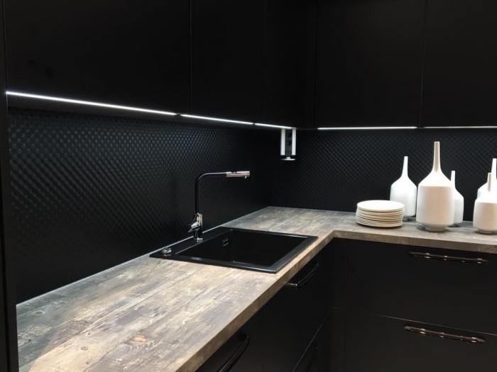 comment décorer une cuisine d'angle aux armoires à fermeture automatique de couleur noir avec comptoir bois massif