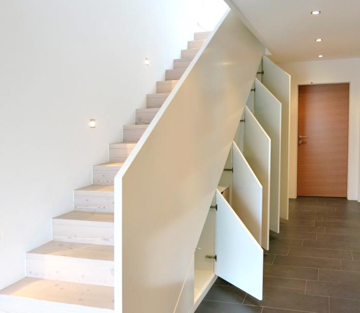 couloir blanc au carrelage de sol gris anthracite et éclairage led sur le plafond avec meuble sous pente
