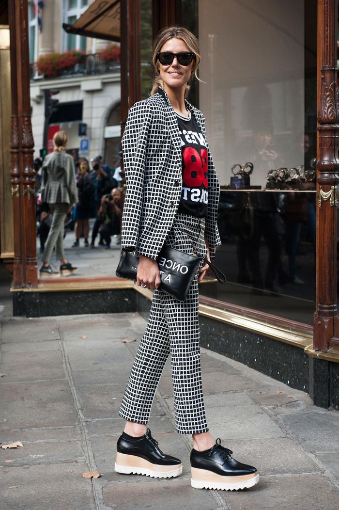 look chic en costume femme à carreaux noir et blanc associé avec un t-shirt graphique, un sac pochette imprimée de lettres et des chaussures compensées