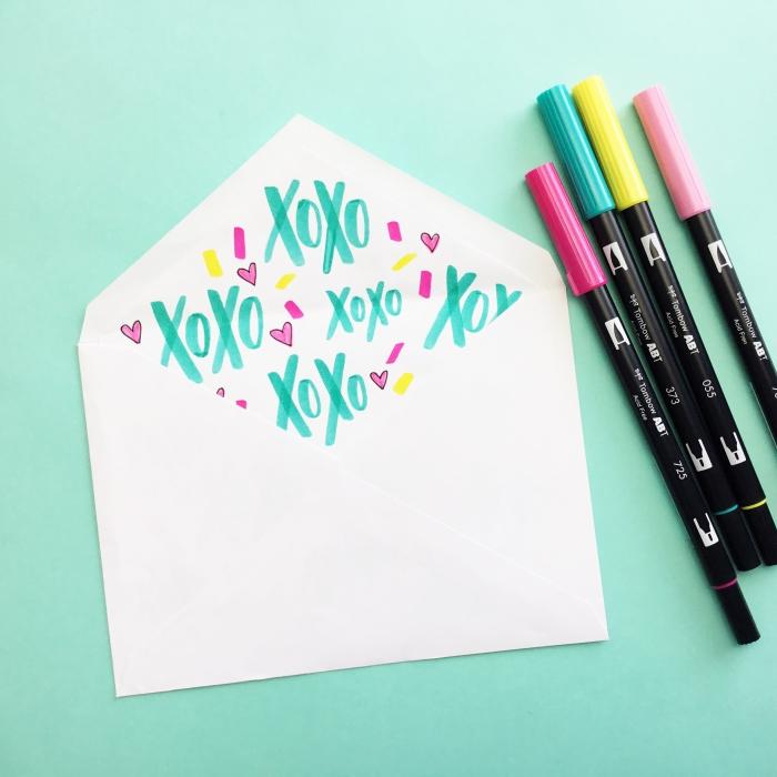 idée comment customiser une enveloppe blanche avec dessins et mots réalisés avec crayons en couleurs variées
