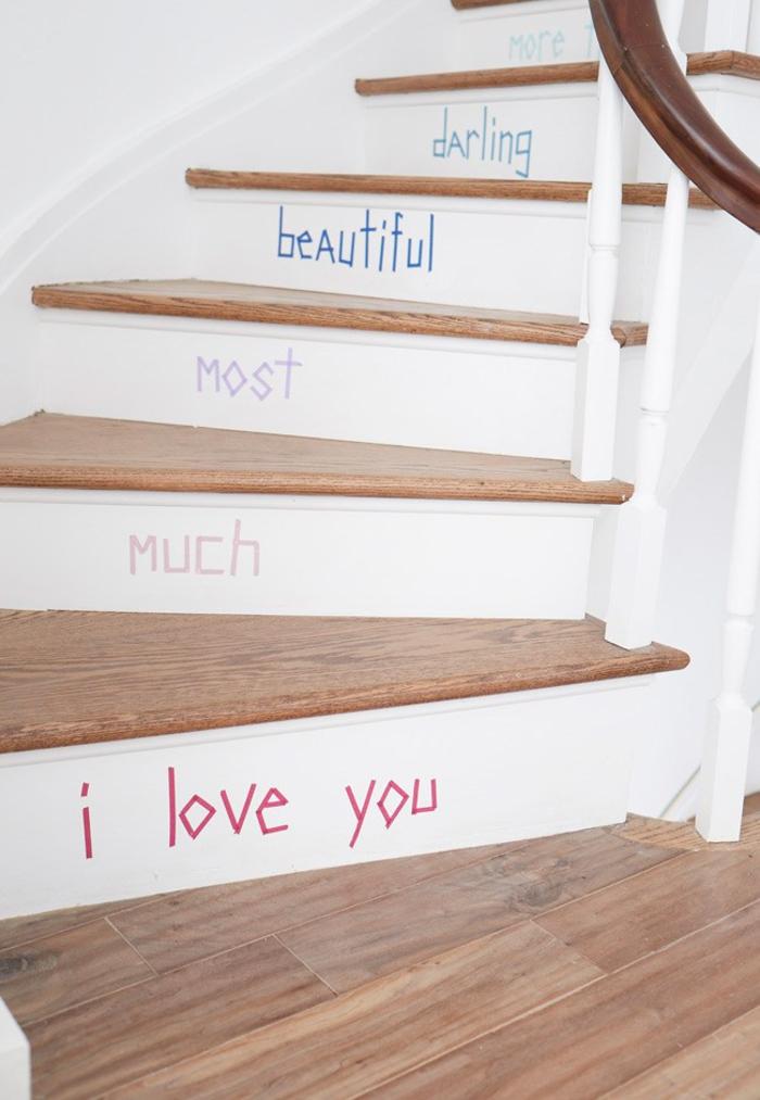 astuces déco pour renover un escalier en bois avec un petit budget, des contre-marches repeintes en blanc portant un message réalisé au masking tape