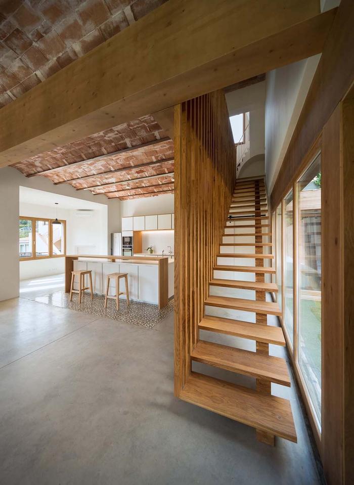 cage d'escalier en bois avec une rambarde au design contemporain qui s'inscrit dans la déco de style loft