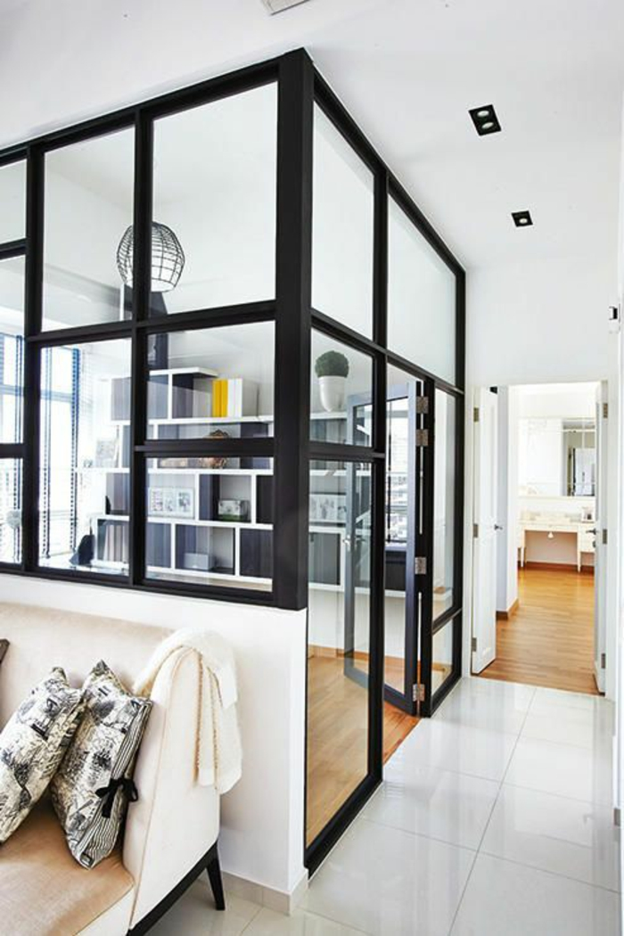 séparation chambre salon, en métal noir avec des vitres blanches transparentes, dalles blanches, parquet en PVC