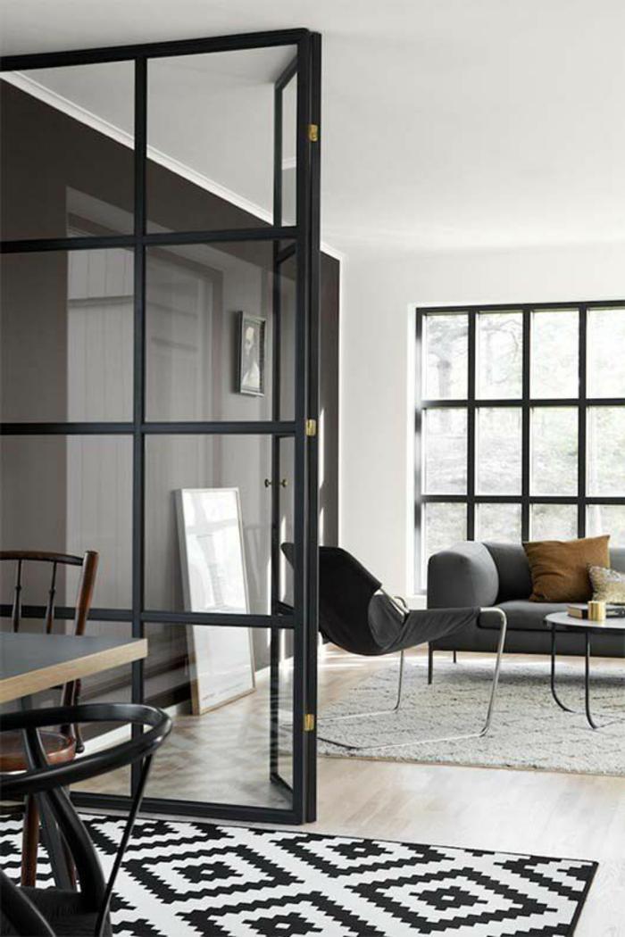 separation verriere en métal noir, avec des vitres blanches transparentes, tapis aux losanges en noir et blanc, parquet en PVC lisse, canapé et fauteuil large en couleur grise