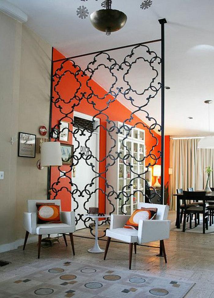 cloison separation en fer forgé noir, motifs arabesques, hauteur du panneau jusqu'au plafond, deux fauteuils blancs, tapis carré en blanc avec des cercles marrons, beiges et bleu pastel
