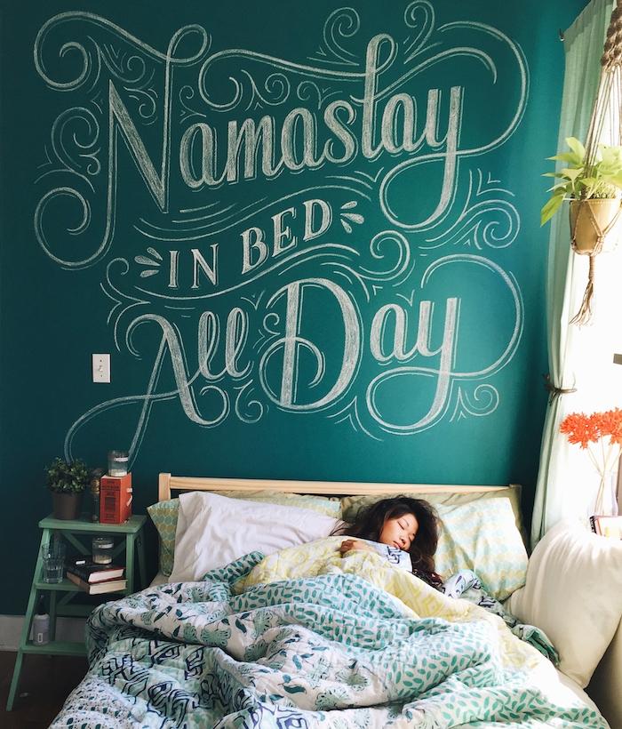 exemple d amenagement chambre avec lit en bois, linge de lit exotique à motifs floraux, et mur de fond en peinture à la craie, chambre cocooning