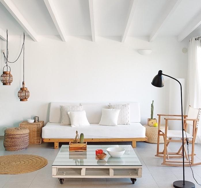 modele de table basse en bois de palette avec plateau en verre et roulettes, canapé en bois avec coussin blanc, carrelage gris, boite rangement rotin