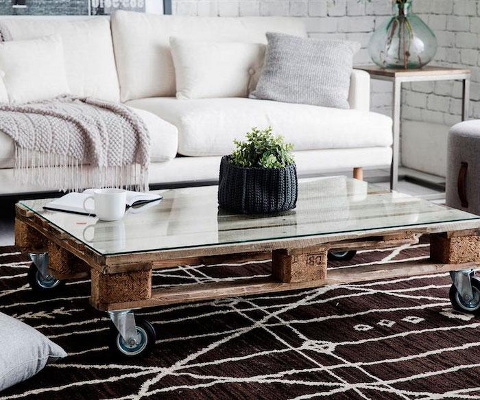 table basse palette de vois, façon rustique avec plateau en verre et des roulettes, canapé blanc cassé, tapis marron