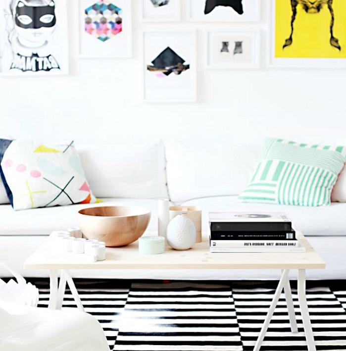 idée pour fabriquer table basse en bois et pieds de metal, tapis noir et blanc, canapé blanc, coussins colorés, deco murale cadres art abstrait, accessoires deco scandinave