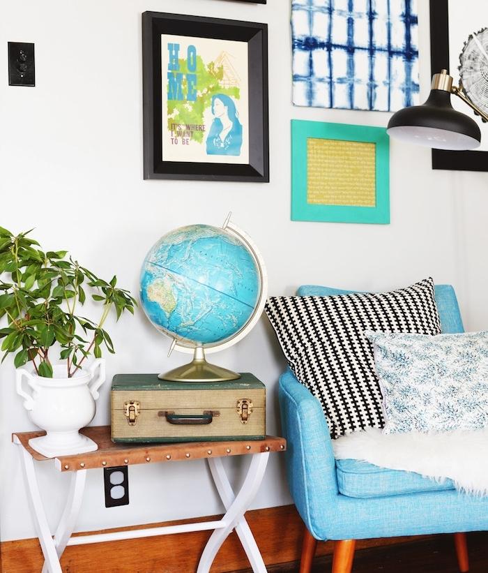 comment fabriquer table basse, table en pieds blancs de bois et plateau de cuir marron, fauteuil bleu, mur de cadres, petite valise vintage