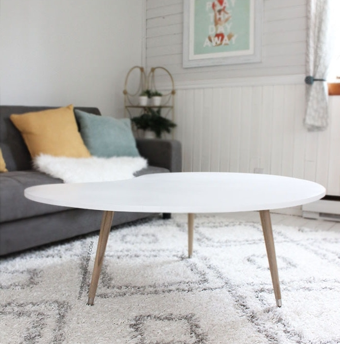 fabriquer sa table basse en plateau de contre plaqué découpe en forme intéressante et repeint en blanc et pieds en bois blond, tapis blanc et gris, canapé gris, coussins colorés