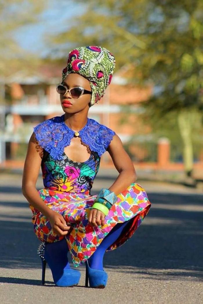 femme africaine avec turban en fuchsia et vert réséda, robe africaine, jupe longue africaine, collants en bleu électrique, bracelets colorés massifs