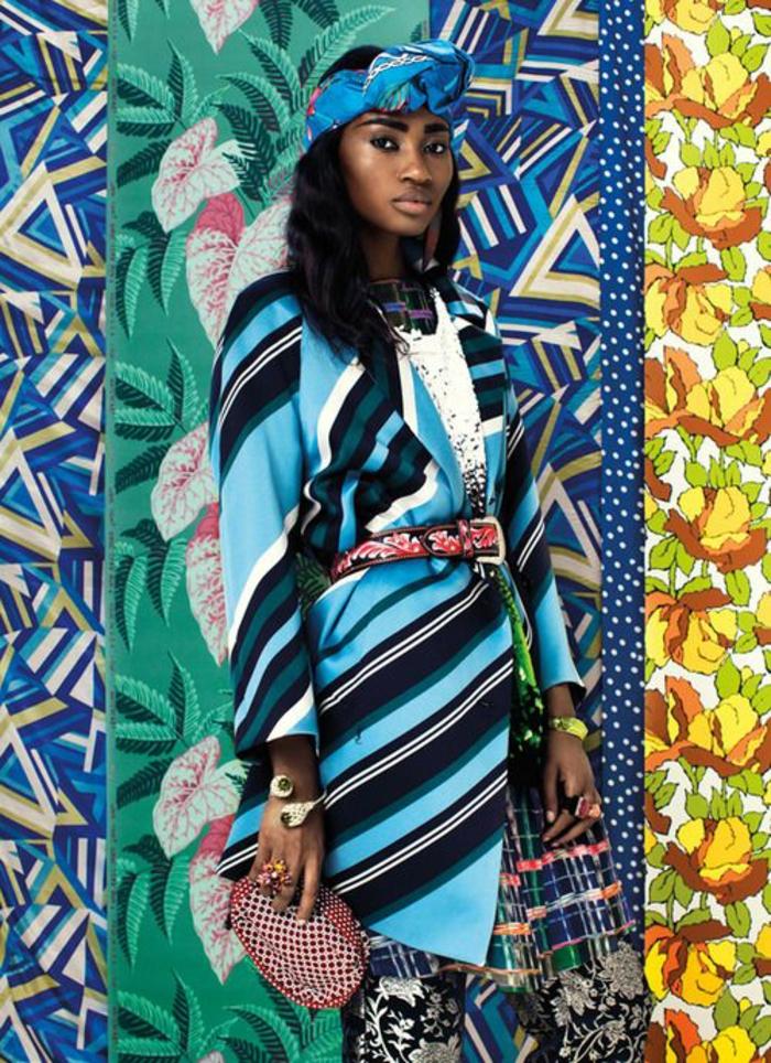 femme avec diadème en tissu coloré sur sa longue chevelure bouclée, jupe longue africaine, style pagne africain, rayures et motifs floraux