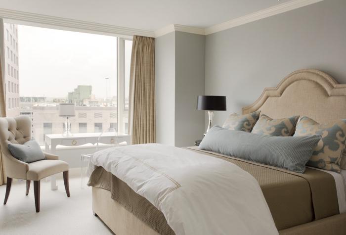 lit kingsize avec tête beige couvert de linge taupe et coussins décoratifs en gris et beige, déco en couleurs neutres et pastel