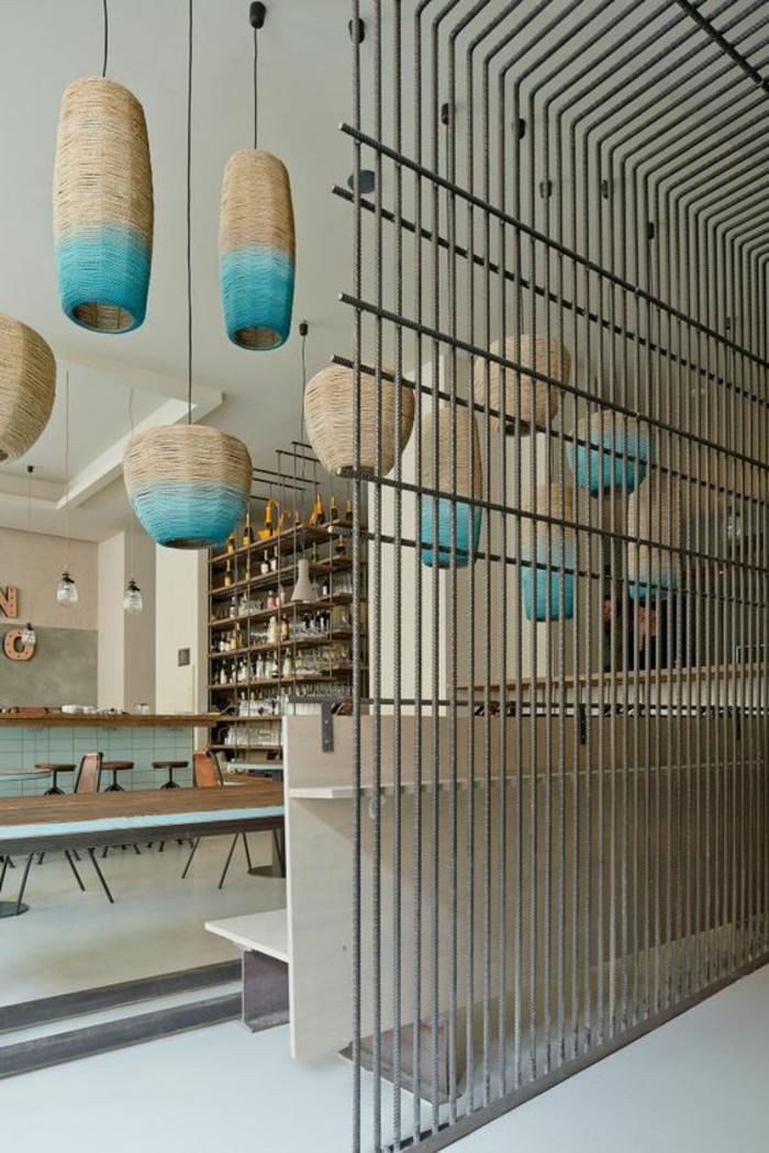 séparation chambre salon, des barreaux verticaux en métal gris, luminaires oblongues en beige et bleu turquoise