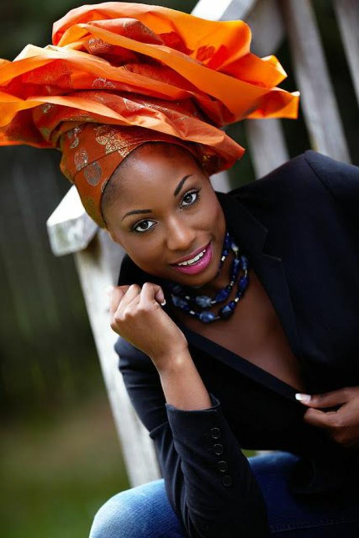 turban en orange noué pour former une fleur avec des grandes pétales, tenue africaine, motif africain, veste en noir décolleté profond, collier avec des pierres amethystes
