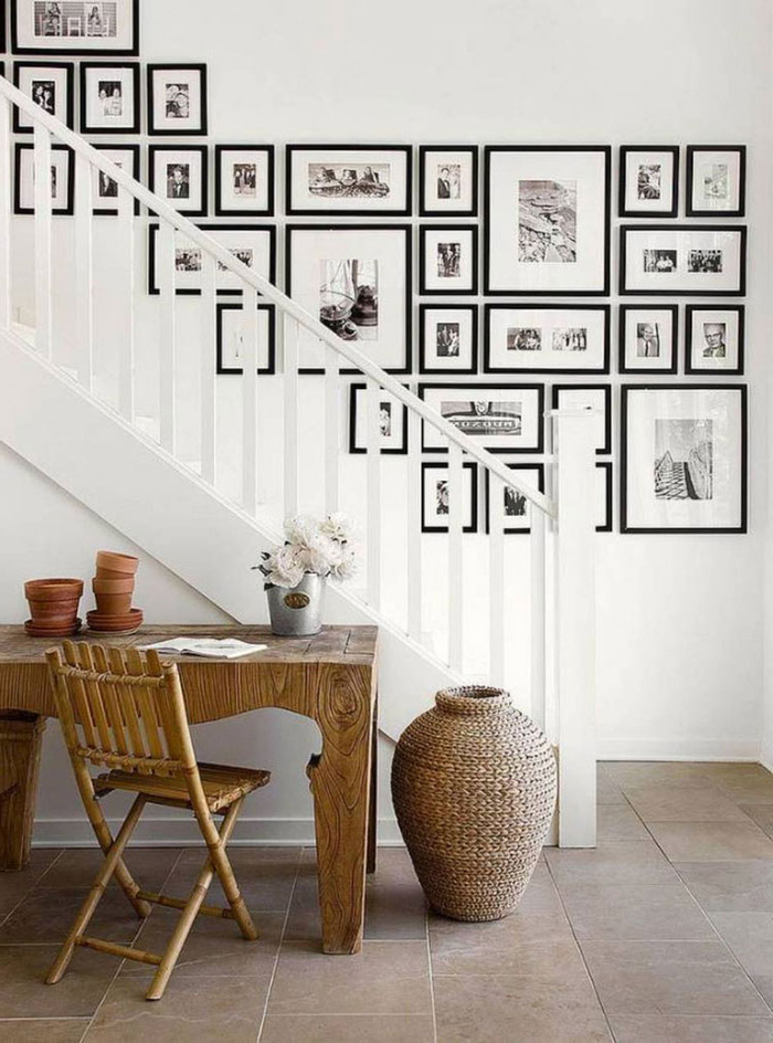 idée pour un mur en cadres photos noir et blanc disposés harmonieusement et en jolie contraste avec l'escalier repeint en blanc