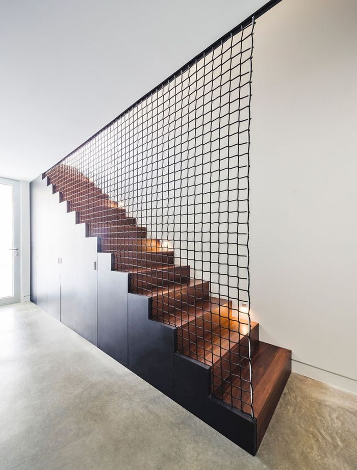 cage d'escalier au design contemporain et aux lignes épurées entièrement en bois avec un garde-corps filet métallique
