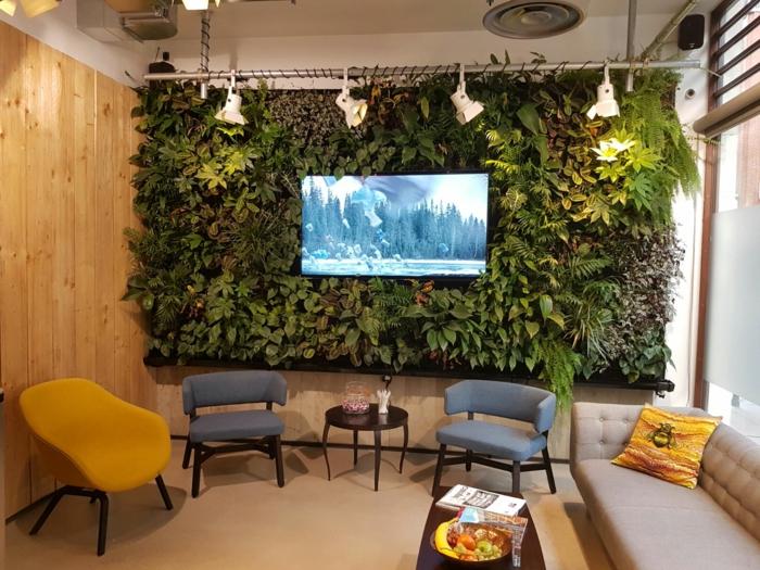 chaises scandinaves, joli mur vert, panneau végétalisé encadrant la tv, petite table basse