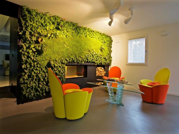 fauteuils en vert et orange, table basse en verre, écran végétalisé et sol gris