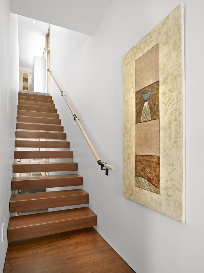 cage d'escalier au design minimaliste décoré d'un grand tableau en tons chauds qui s'harmonise avec l'escalier en bois