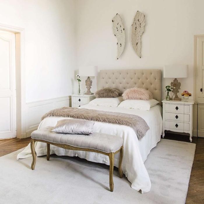 peinture murale blanche dans la chambre adulte avec lit en tête beige boutonné et large tapis gris clair