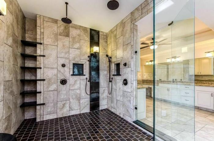 cabine de douche avec rangement mural, travertin aux murs, sol mosaique noir