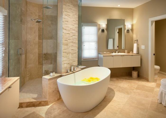 idée déco salle de bain avec travertin, baignoire en jolie forme ovale, petit miroir suspendu, espace douche
