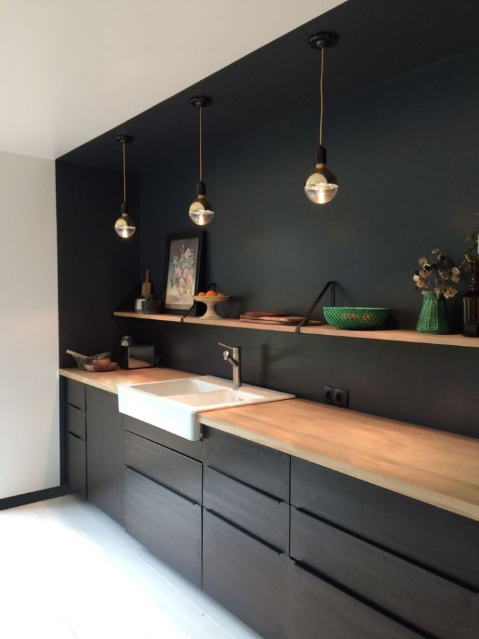 modèle de lampes suspendues en noir et cuivre, cuisine aménagée en longueur avec comptoir de bois clair