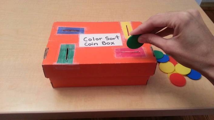 jeu pédagogie montessori en crèche pour apprendre les couleurs, insérer des monnaies colorées dans les fentes correspondantes d une boite en carton, montessori materiel diy