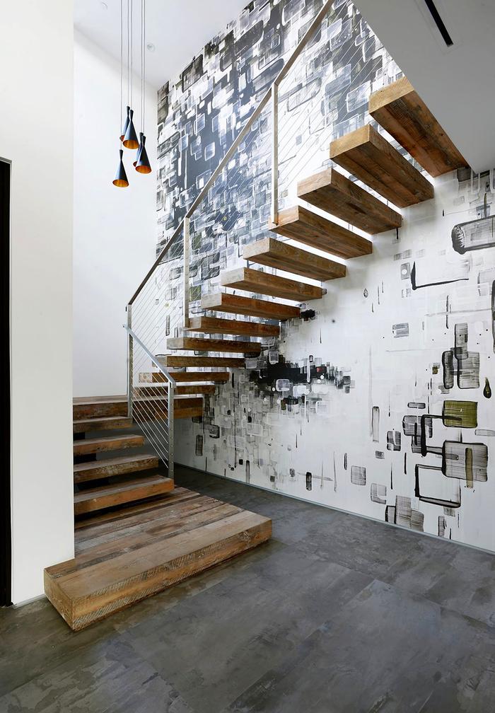 une cage d'escalier de style industriel au mur revêtu de papier peint graphique qui fait ressortir les marches en bois