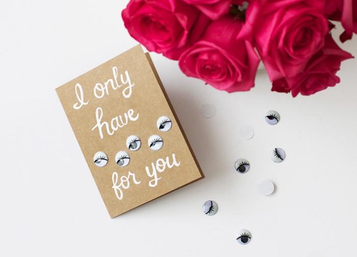 une carte saint valentin originale en papier kraft, décoré des yeux en blanc et gris avec texte blanc, bouquet de roses, idee cadeau saint velentin simple