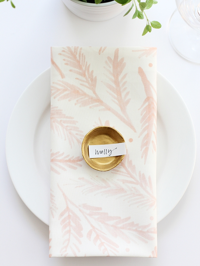 comment faire une marque place originale, modele pate fimo coupelle dorée avec étiquette contenant le nom de l'invité, serviette blanche à motif floral, déco table originale