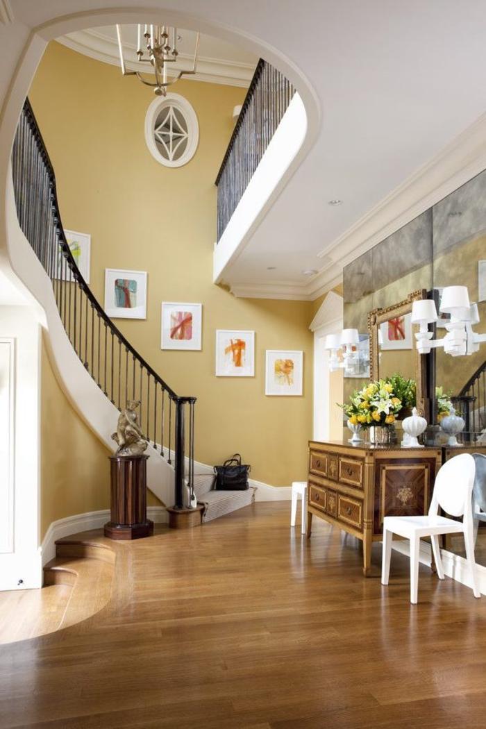 cage d'escalier au design classique peinte en couleur ocre et dynamisée par une galerie de tableaux accrochés de façon symétrique