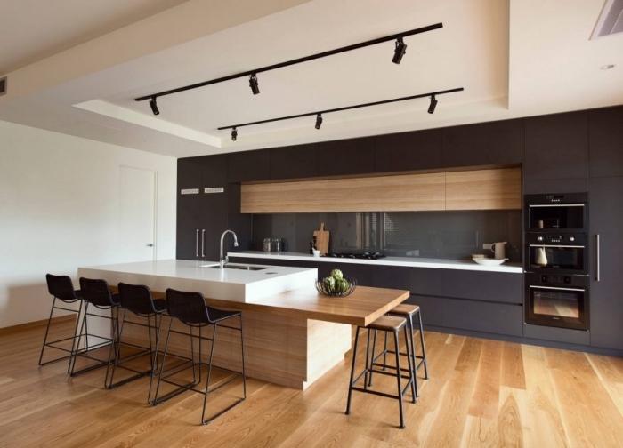 modèle de chaises et tabourets de bar noirs sur un plancher de bois clair, cuisine bois et noir aménagée en longueur