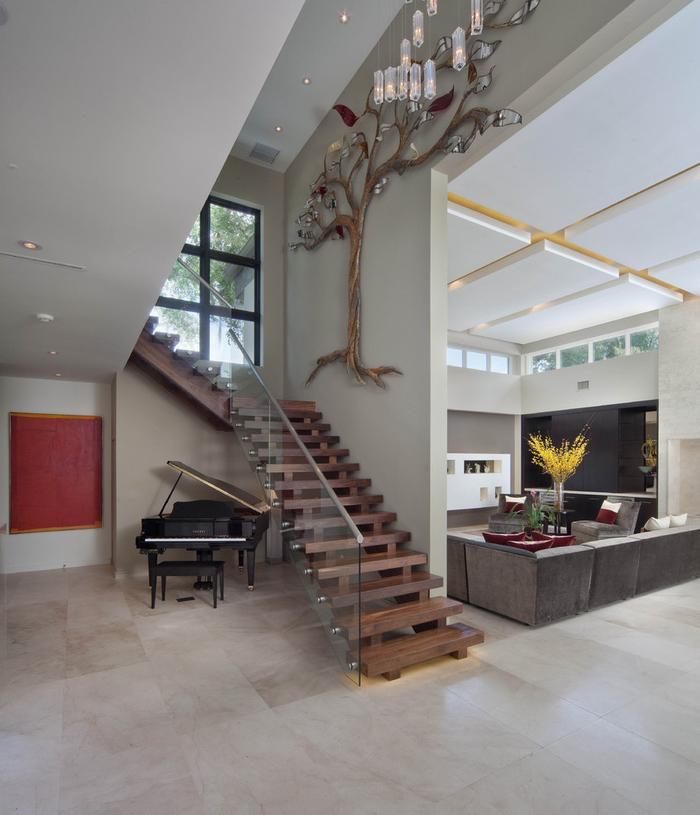escalier en bois au design contemporaine et aux lignes épurées avec un garde-corps en verre agrémenté d'une déco murale originale en forme d'arbre