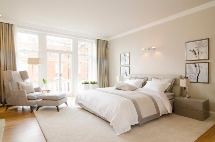comment intégrer la couleur ecru dans la chambre blanche avec fauteuil et tabouret moderne de nuance gris pastel