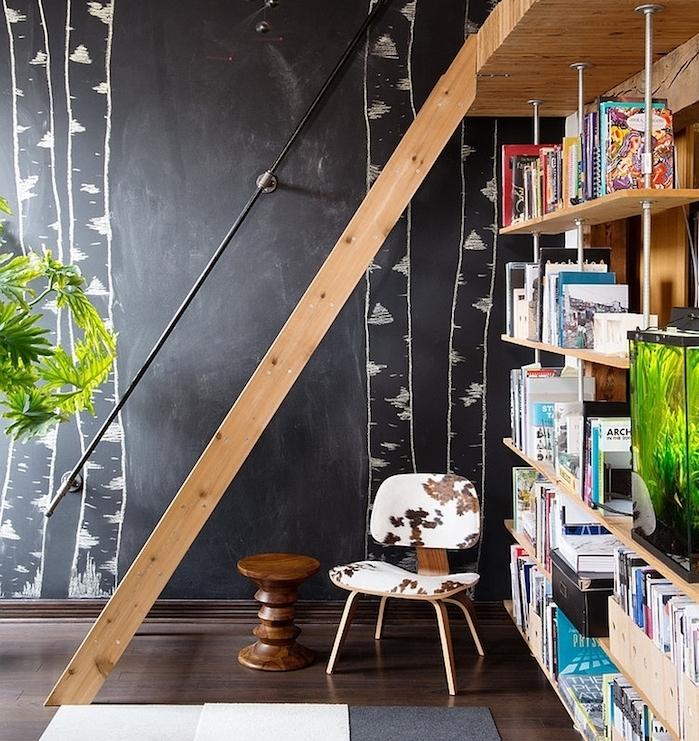modele de bibliothèque en bois à tubes metalliques, parquet marron foncé, escalier droit en bois, mur repeinte en peinture craie aux arbres dessinés à la craie
