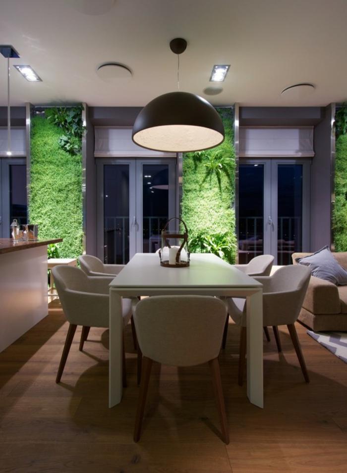 jardin vertical, lampe suspendue noire, murs en mousse verte, table blanche et chaises blanches