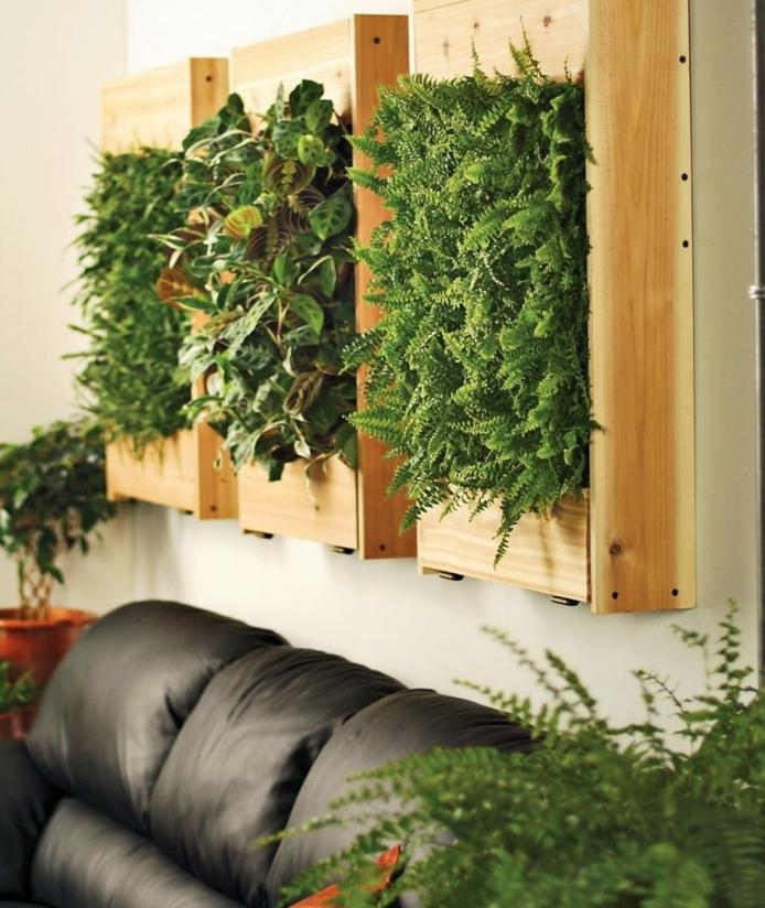 grand sofa noir, mur vert composé de trois encadrements, décoration vivante