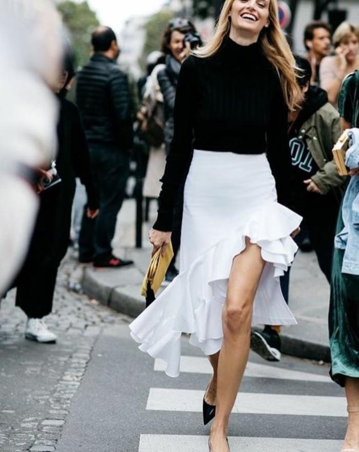 look classique avec jupe blanche asymétrique, haut chic bas choc, longueur mini et longueur maxi avec gros volants en diagonale, pull noir classique avec col tortue