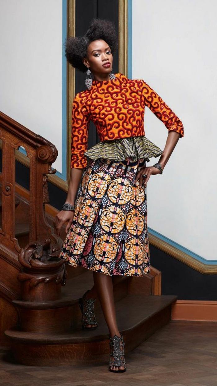 veste en orange avec des arabesques rouges, jupe longue africaine avec des plissés larges, veste à volants sur la taille, sandales gris anthracite avec des lacets