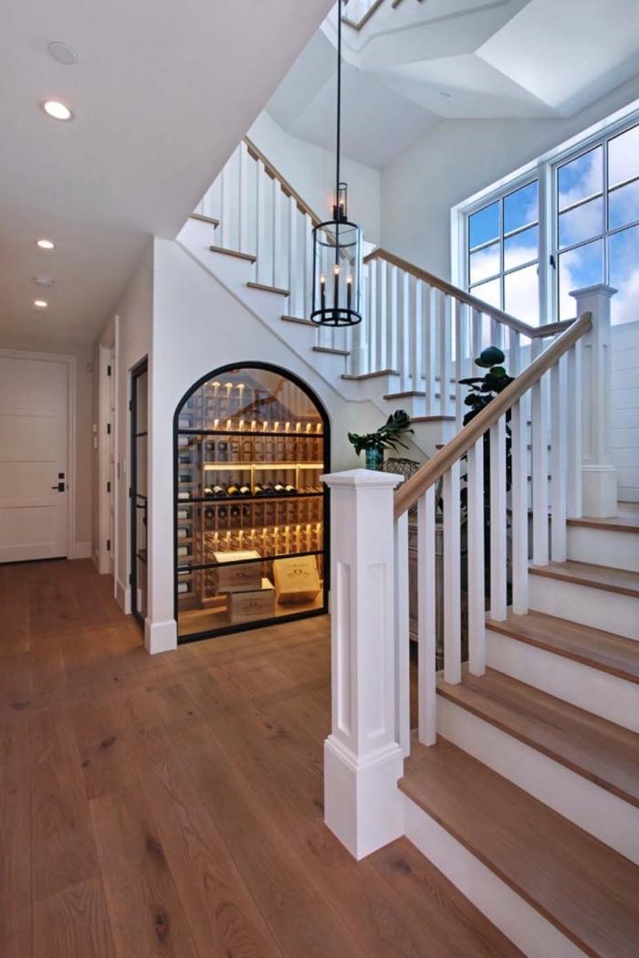 rangement sous escalier en verre pour stocker les bouteille de vin, design intérieur dans le couloir blanc avec parquet de bois