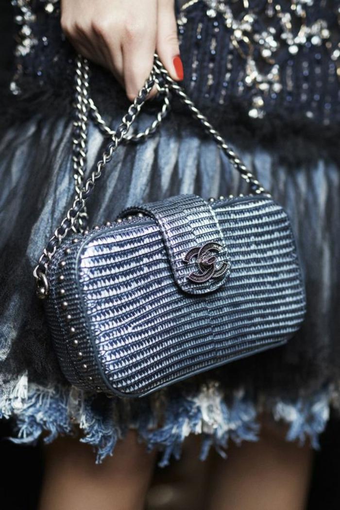 mini sac Chanel aux nuances irisées, avec le logo en métal noir, chaînette en métal couleur argent, jupe aux ourlets en petites plumes couleur blanche et grise, soirée chic et choc comment s habiller