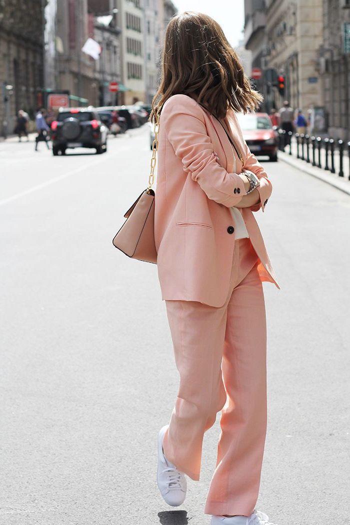look masculin féminin en tenue femme fluide en couleur rose poudré combiné avec des baskets blancs pour une silhouette décontractée et chic