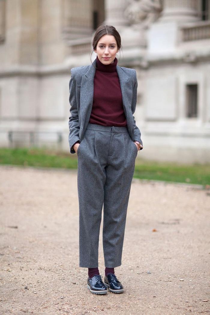 un ensemble tailleur femme chic de coupe garçonne couleur gris anthracite porté associé à un pull à col roulé bordeaux et des derbies noires