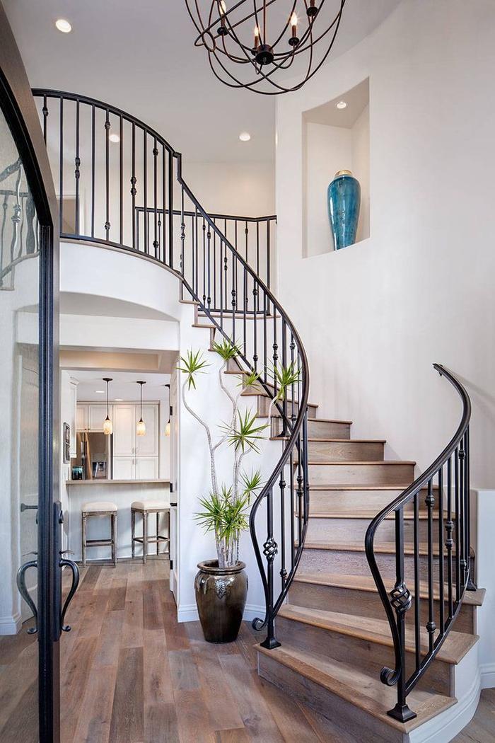 idée pour une deco montee escalier de style méditerranéen avec jolie rambarde de fer forgé et un luminaire en suspension en fils de fer